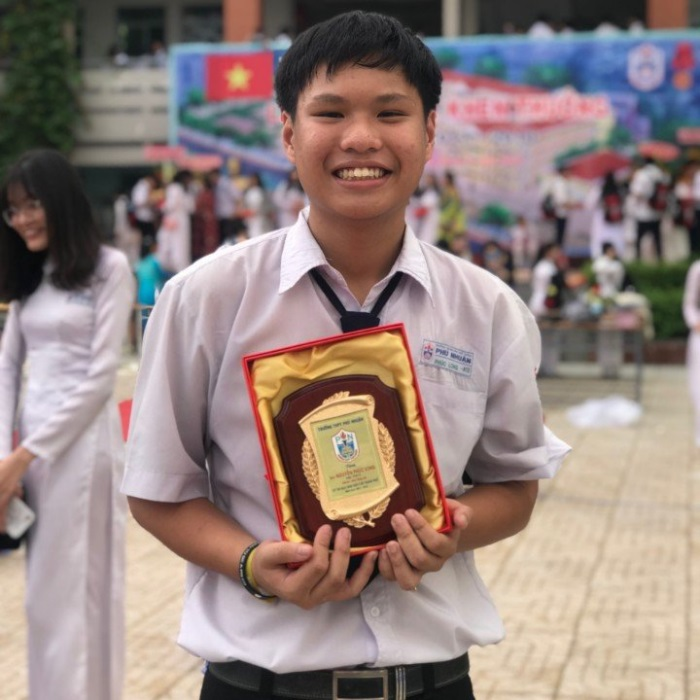 Portrait of long smiling in the street while holding a silver medal for gifted student